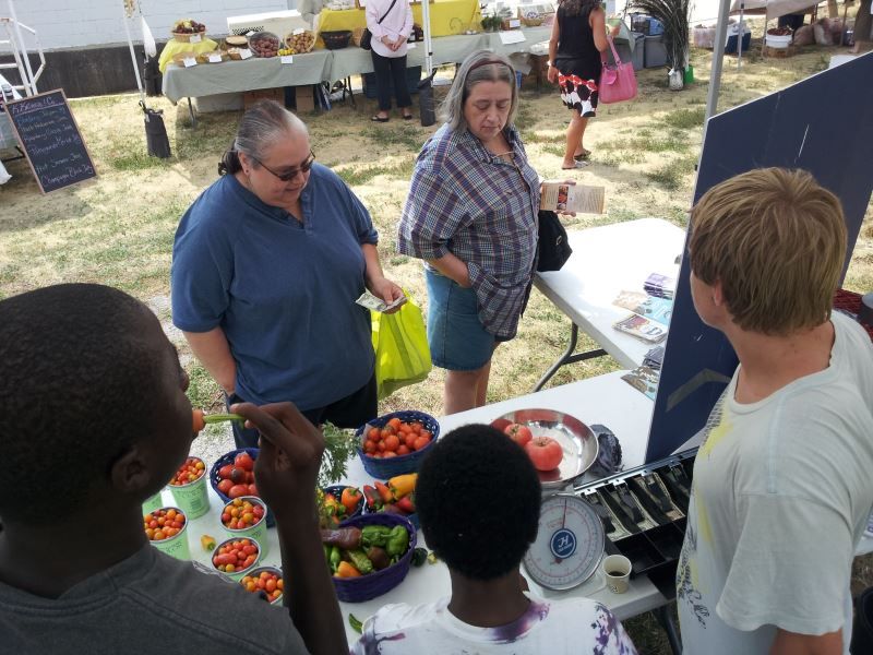 Youth selling home-grown vegetables to the public.